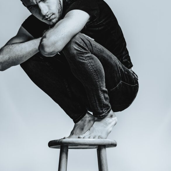 man squatting on stool crossing his arms