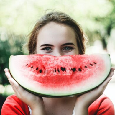 woman holding sliced watermelon