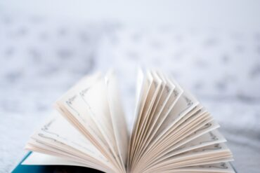 opened book on white textile